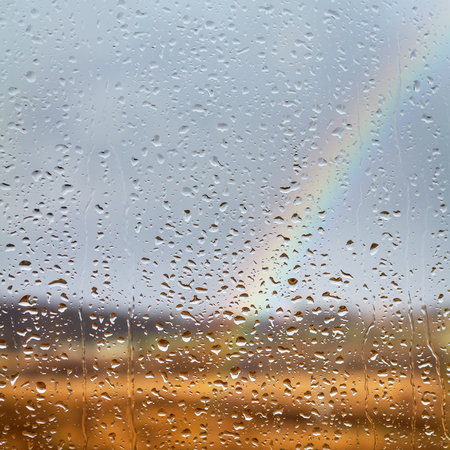 raindrops: Rainbow through rained window with droplets Stock Photo