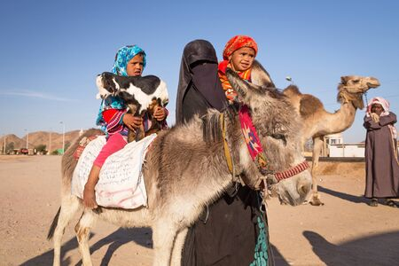 muslim baby girl: Arabic family with goat and donkey on the local bus station near Hurghada Editorial