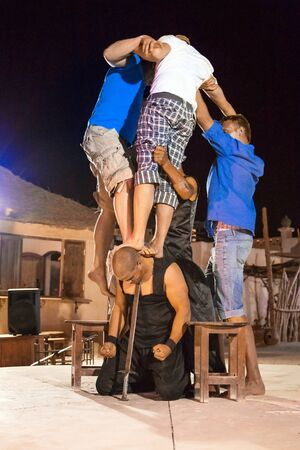 swallowing: People at a performance called Fakir show with sword swallowing on the desert at Hurghada
