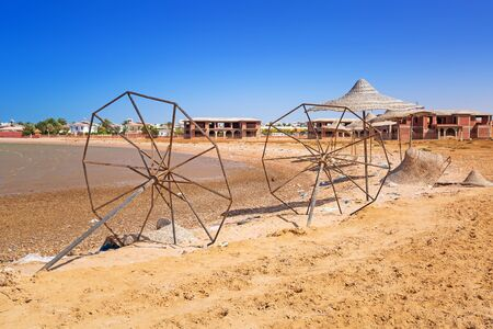 devastated: Devastated beach with broken parasols at Red Sea in Egypt