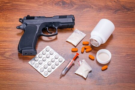 narcotics: Set of narcotics and handgun on wooden table