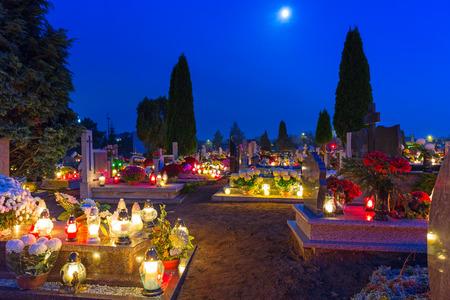 memorial cross: Cementerio por la noche con velas de colores de Todos los Santos en Polonia