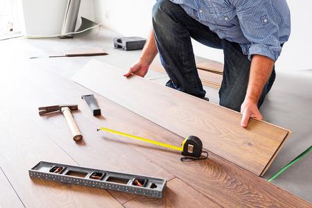 laminated: Man installing new laminated wooden floor