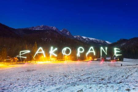 zakopane: Zakopane sign under Tatra mountains at night, Poland Stock Photo