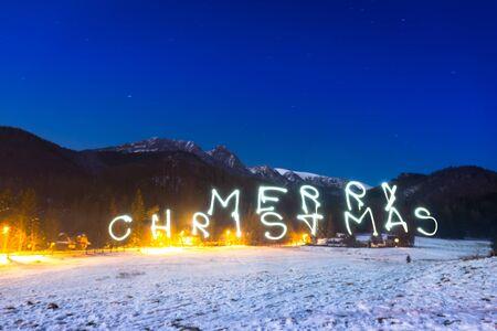giewont: Merry Christmas sign under Tatra mountains at night, Poland Stock Photo