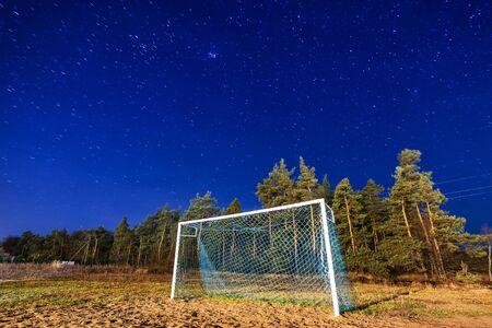 starry night: Soccer pitch under starry sky at night Stock Photo