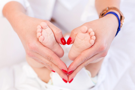 touching toes: Baby feet in mothers hands Stock Photo