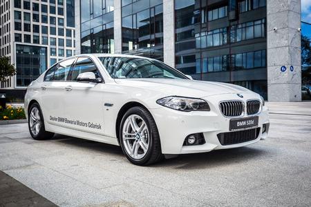 New model BMW 520d in white against modern design buildings in Gdansk