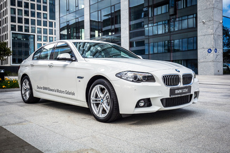 New model BMW 520d in white against modern design buildings in Gdansk