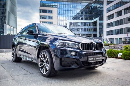 New model BMW X6 in dark blue against modern design buildings in Gdansk