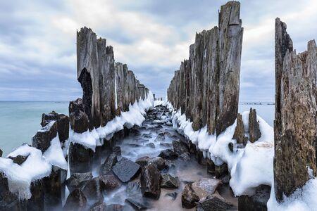 Frozen wooden breakwaters line to the World War II torpedo platform at Baltic Sea, Babie Doly, Poland