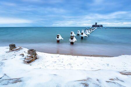 breakwaters: Frozen wooden breakwaters line to the World War II torpedo platform at Baltic Sea, Babie Doly, Poland Stock Photo