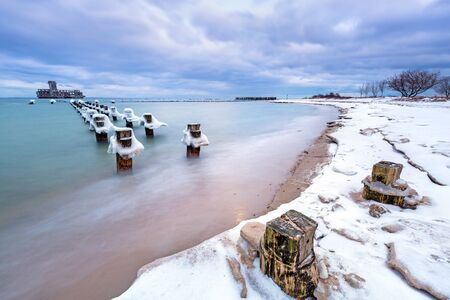 Babie: Frozen wooden breakwaters line to the World War II torpedo platform at Baltic Sea, Babie Doly, Poland Stock Photo