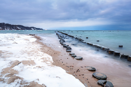 breakwaters: Frozen wooden breakwaters line to the World War II torpedo platform at Baltic Sea, Babie Doly, Poland Stock Photo
