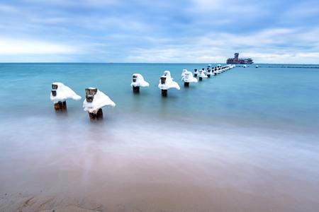 babie: Frozen wooden breakwaters line to the World War II torpedo platform at Baltic Sea, Babie Doly, Poland Stock Photo