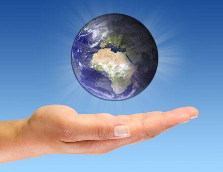 glowing earth: Glowing earth on open palm Stock Photo