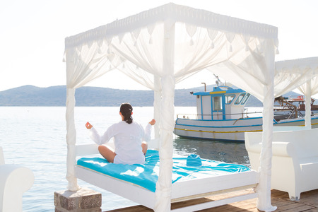 luxurious: Woman meditating on luxurious resort bed at the sea