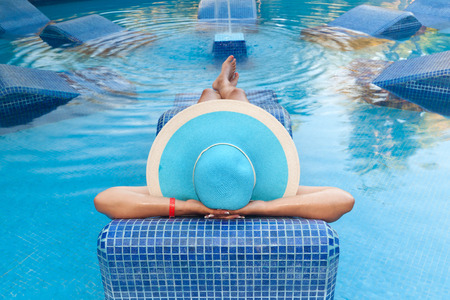 unwind: Woman relaxing on swimming pool bed Stock Photo