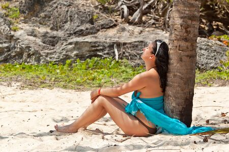destress: Beautiful woman sitting under palm tree at the beach