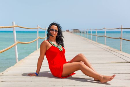 Beautiful woman in red dress posing on the pier by the beach Stock Photo