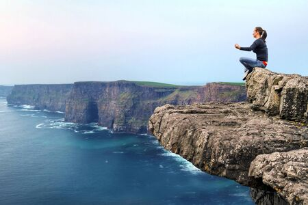 Mujer meditando en el borde del acantilado