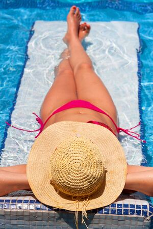 destress: Woman in hat relaxing on swimming pool bed Stock Photo