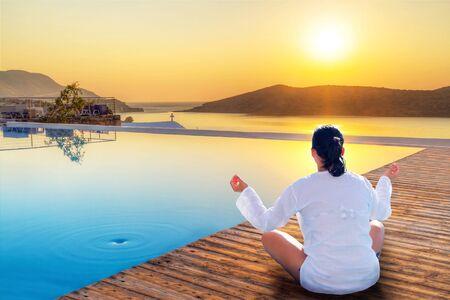 Frau meditiert am Pool bei Sonnenaufgang