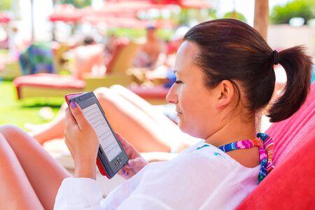fiestas electronicas: Lectura de la mujer en el libro electrónico en vacaciones de verano Foto de archivo