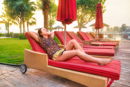 destress: Woman relaxing on deckchair at sunrise Stock Photo
