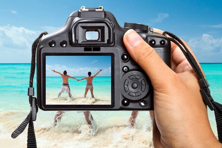 capturing: Photographer capturing rear view of happy couple by the beach