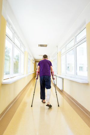 kneecap: Man walking with crutches after arthroscopic surgery
