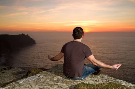 moher: Man meditating on Cliffs of Moher