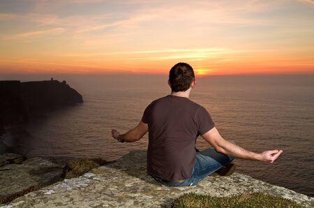 man meditating: Man meditating on Cliffs of Moher