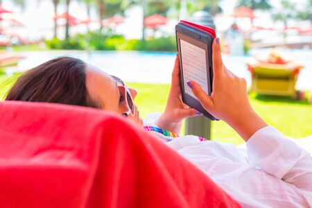 fiestas electronicas: Woman reading on electronic book on summer holidays