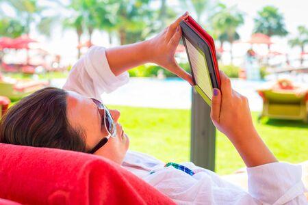 fiestas electronicas: Lectura de la mujer en el libro electr�nico en vacaciones de verano Foto de archivo