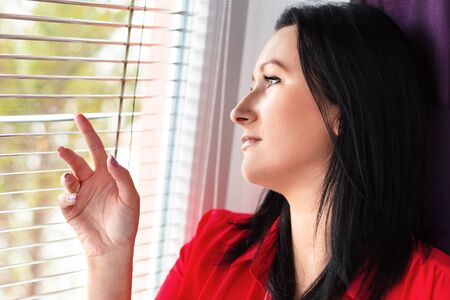 jalousie: Beautiful woman looking out of the window through a jalousie Stock Photo