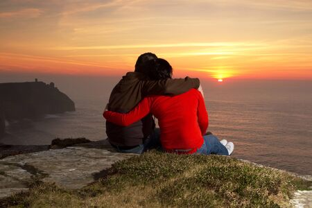 moher: Loving couple watching sunset on Irish Cliffs of Moher