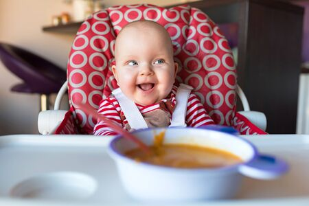 high chair: Baby girl sitting on the high chair for lunch Stock Photo