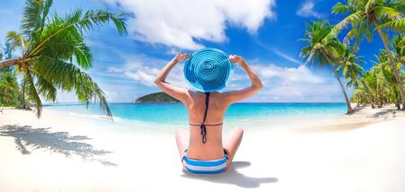 Woman enjoying the sun by the seashore Stock Photo