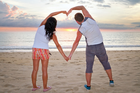 koh kho khao: Romantic couple making heart shape with arms on the beach
