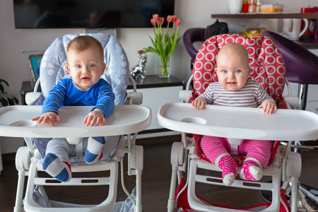 high chair: Baby boy and girl twins sitting on the high chair