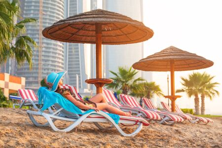 destress: Woman relaxing on deckchair at sunrise in Abu Dhabi