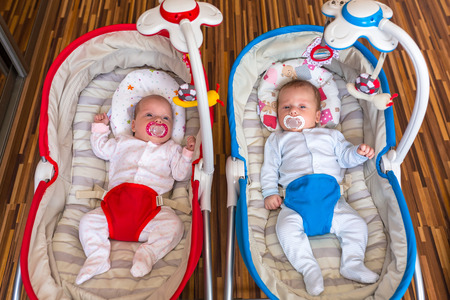 woman hanging toy: Baby girl and boy twins lying down in the cradle Stock Photo