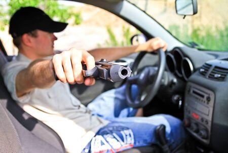 Man holding a gun in the car Stock Photo