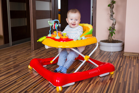 First steps of the boy in a baby walker