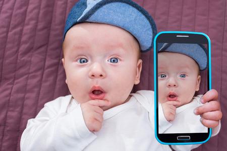 El bebé tomando autofoto con una cámara de teléfono celular Foto de archivo