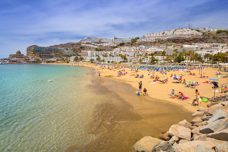 PUERTO RICO, SPAIN - APRIL 21, 2016: Beach of Puerto Rico with many tourists, Gran Canaria. Puerto Rico is a specially constructed holiday resort situated on the south-west coast of Gran Canaria. Editorial