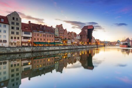 GDANSK, POLAND - 21 JUNE 2016: Medieval port crane over Motlawa river at night. This port crane built between 1442 and 1444 is the symbol of Gdansk and the oldest surviving port crane in Europe. Editorial