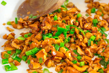 golden chanterelle: Sliced golden chanterelle fungus with chives frying on the pan Stock Photo
