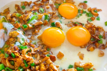 golden chanterelle: Frying eggs with sliced golden chanterelle fungus and chives